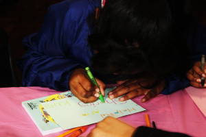 Child drawing in a book on children's day