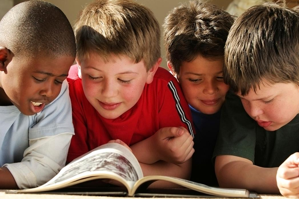 Children happily reading a book together